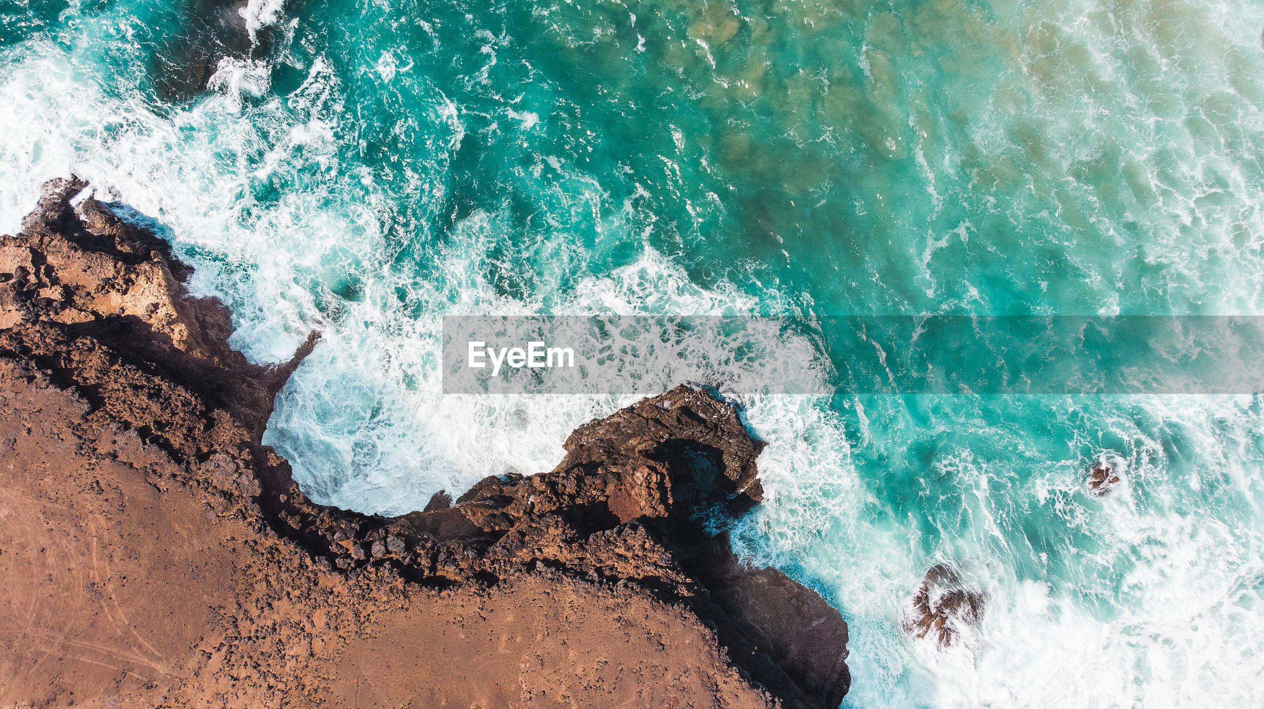 HIGH ANGLE VIEW OF WAVE SPLASHING ON ROCK