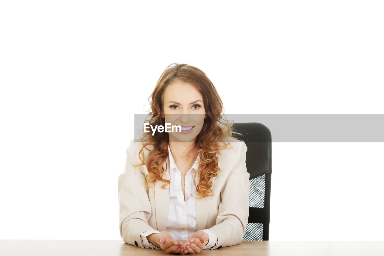 Portrait of smiling businesswoman sitting against white background