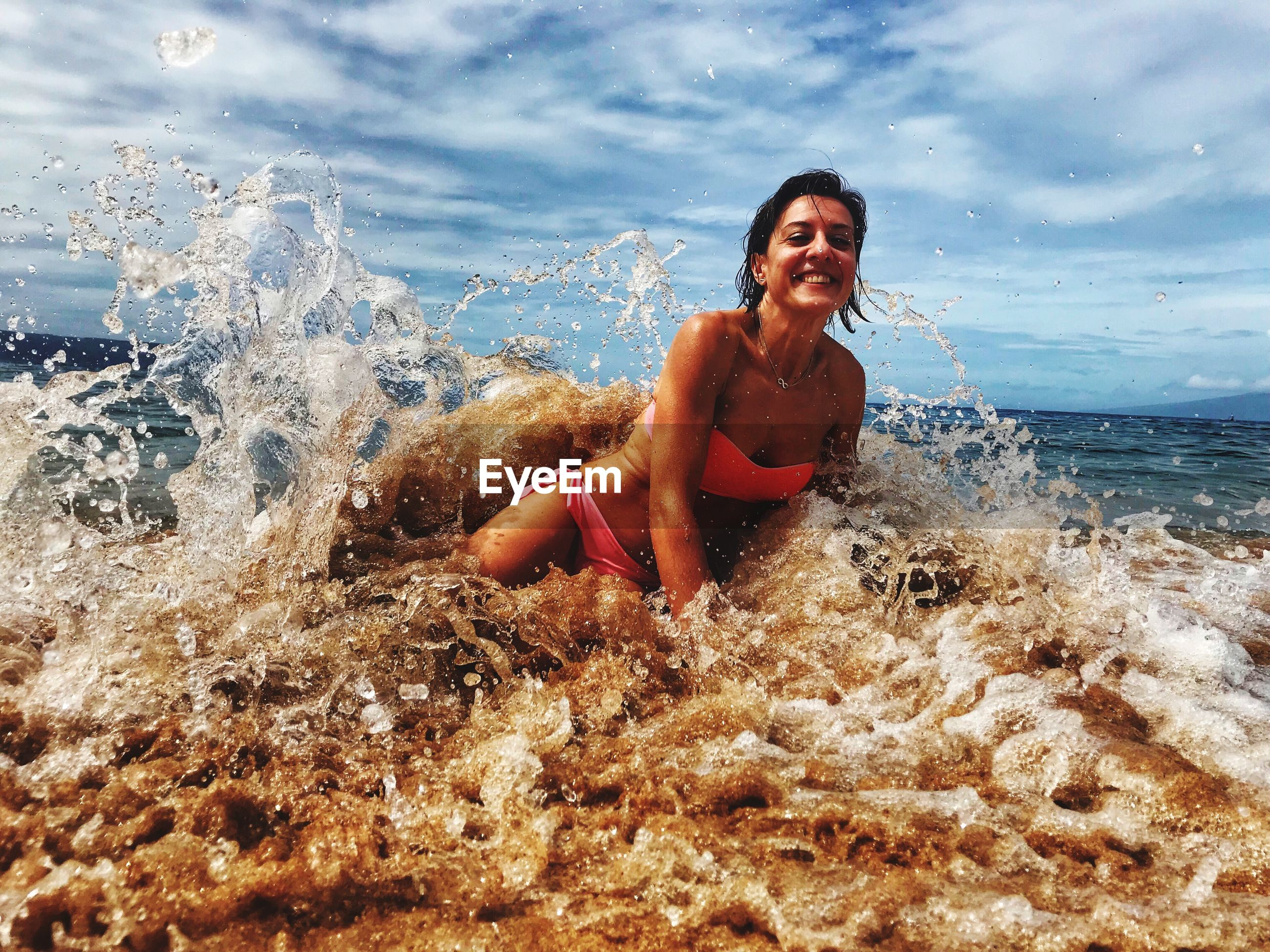 Portrait of smiling woman playing in waves on shore at beach