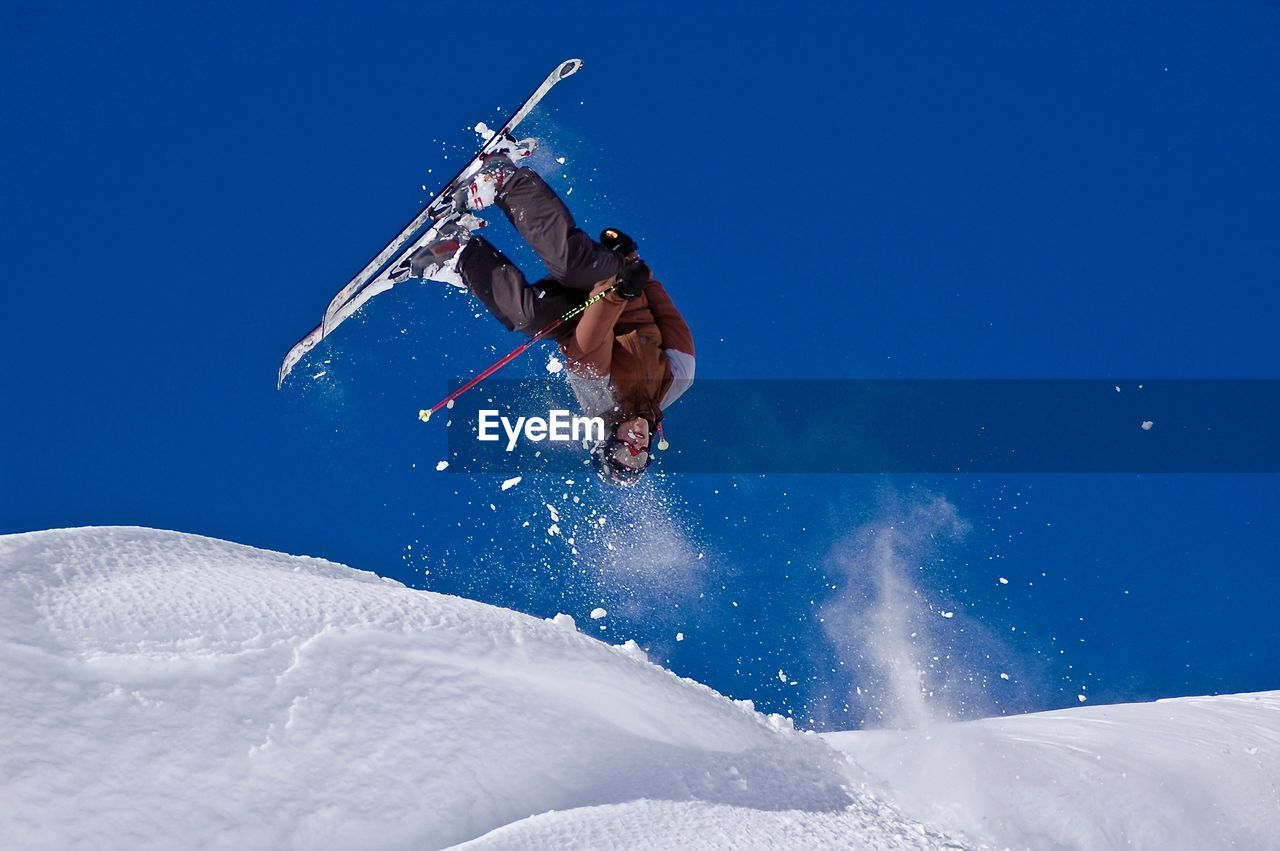 Low Angle View Of Man Jumping On Snowcapped Mountain Against Sky