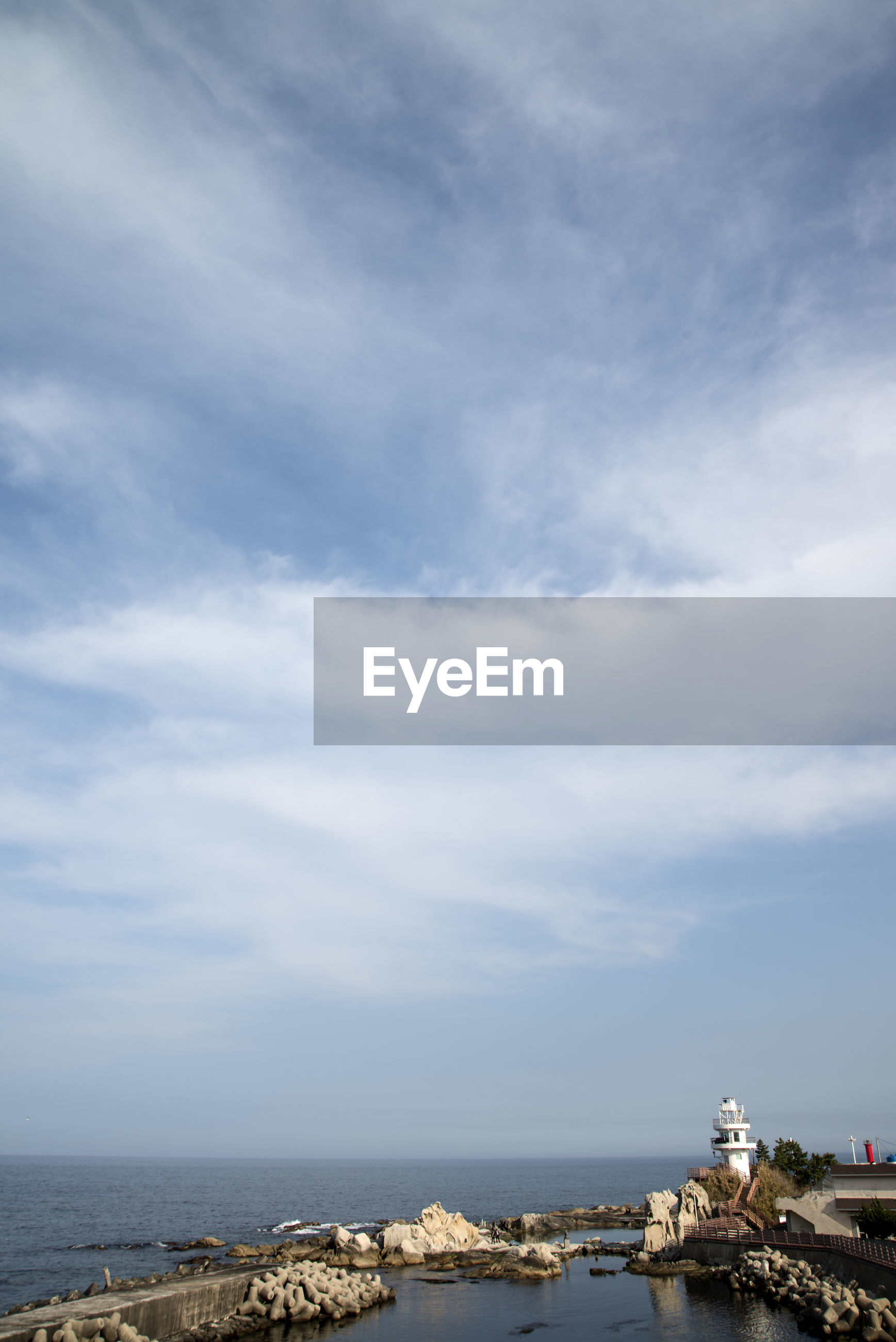 SCENIC VIEW OF SEA BY CITYSCAPE AGAINST SKY