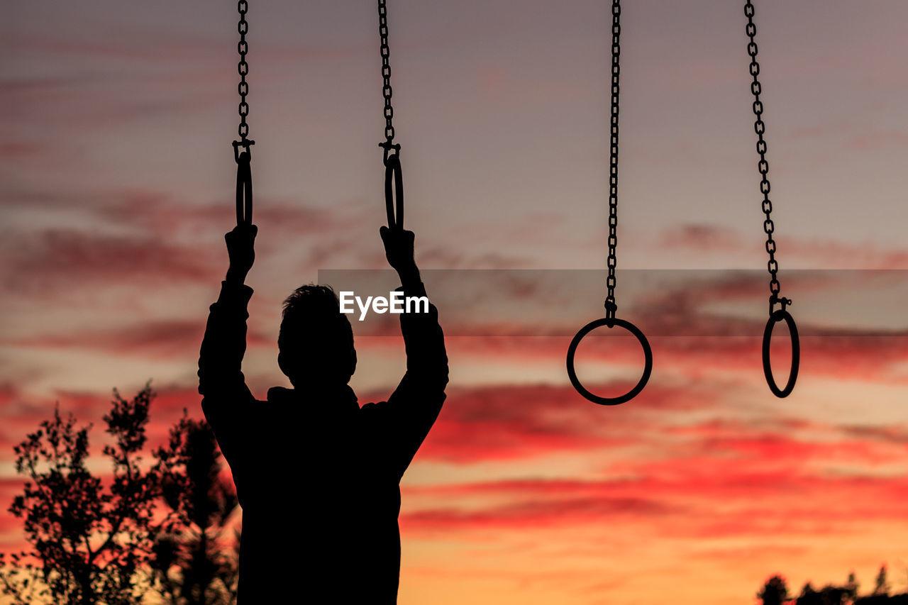 Silhouette Man Hanging On Gymnastic Rings Against Orange Sky