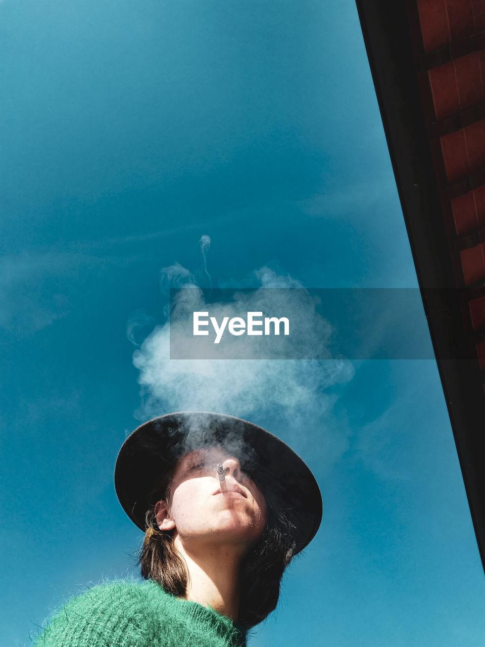 Woman smoking against sky