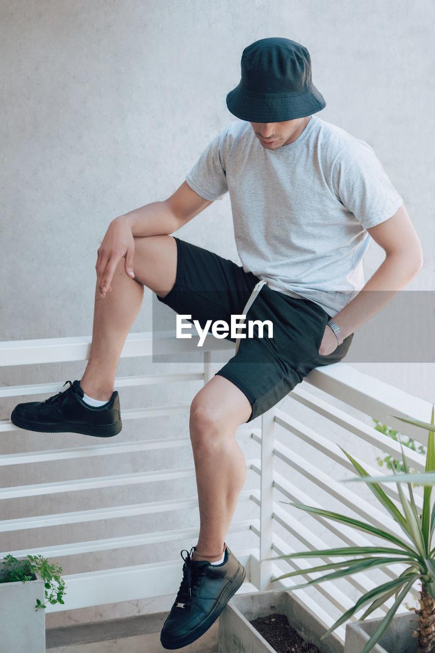 Full length of man sitting on railing against wall