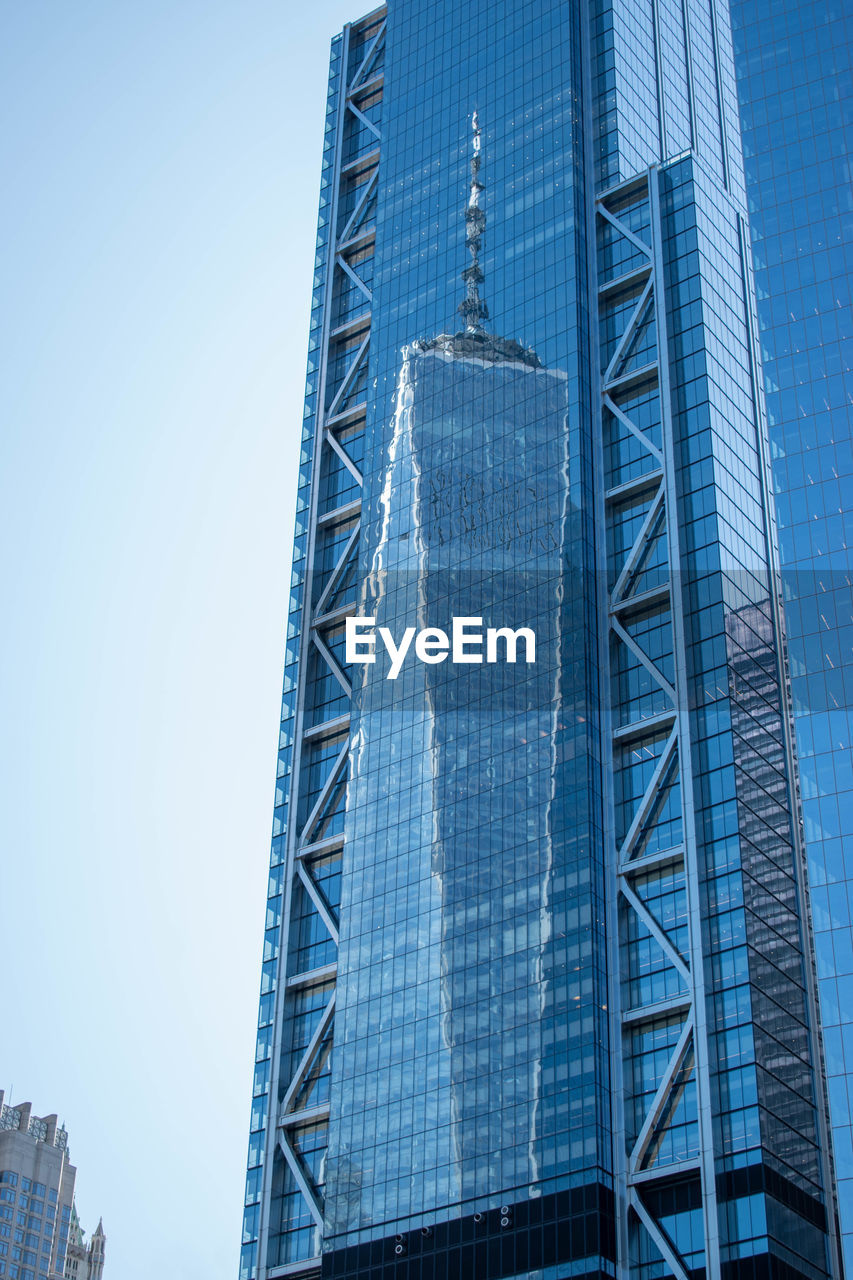 LOW ANGLE VIEW OF MODERN GLASS BUILDING AGAINST CLEAR BLUE SKY