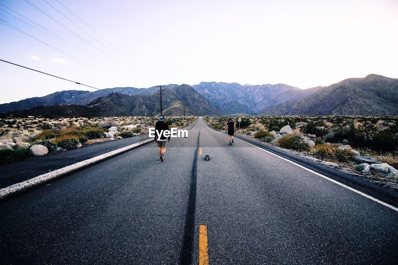 Rear View Of Men Walking On Road Against Mountain Range