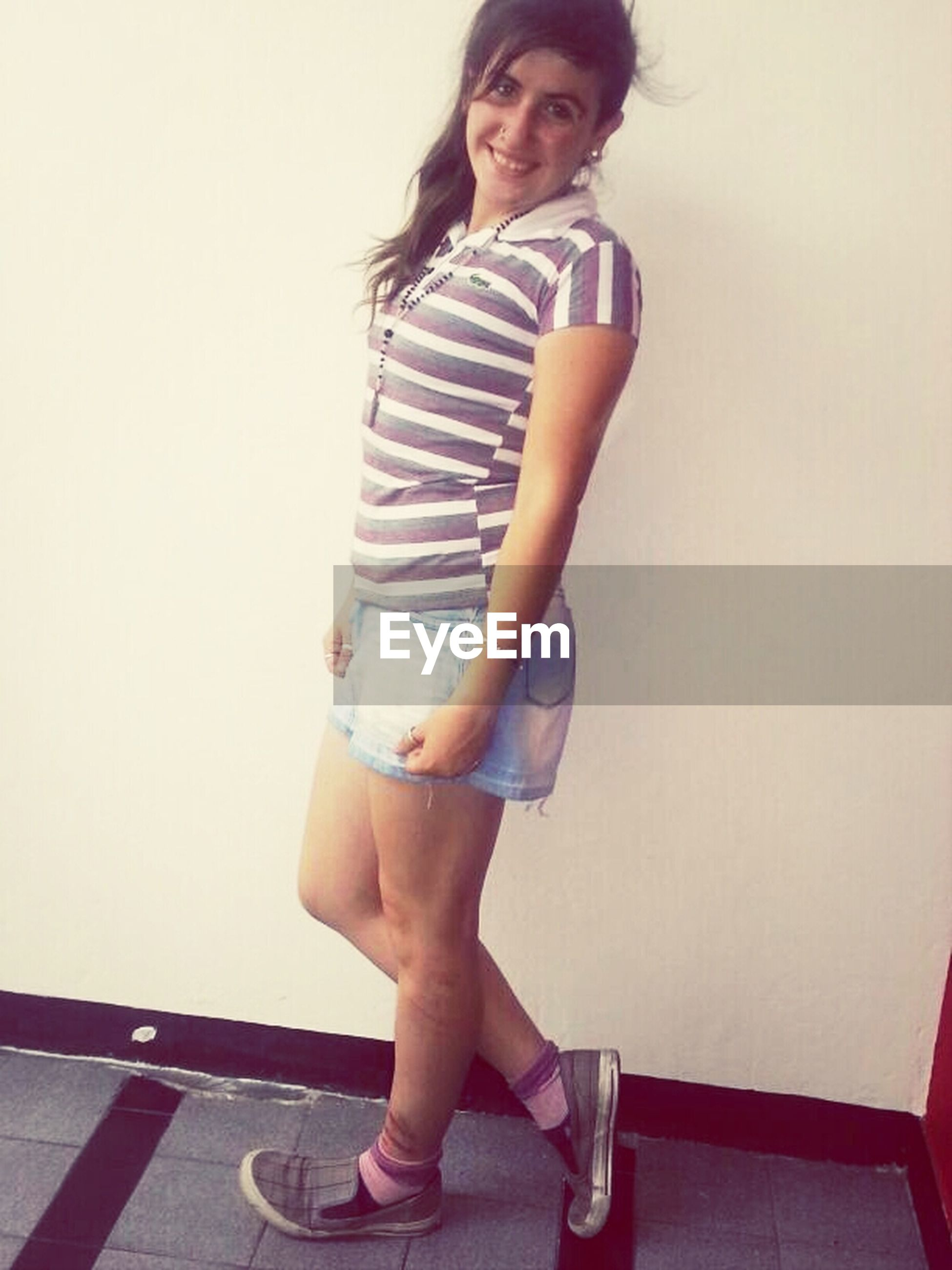 young adult, person, casual clothing, front view, young women, lifestyles, looking at camera, standing, portrait, full length, three quarter length, indoors, leisure activity, wall - building feature, smiling, holding