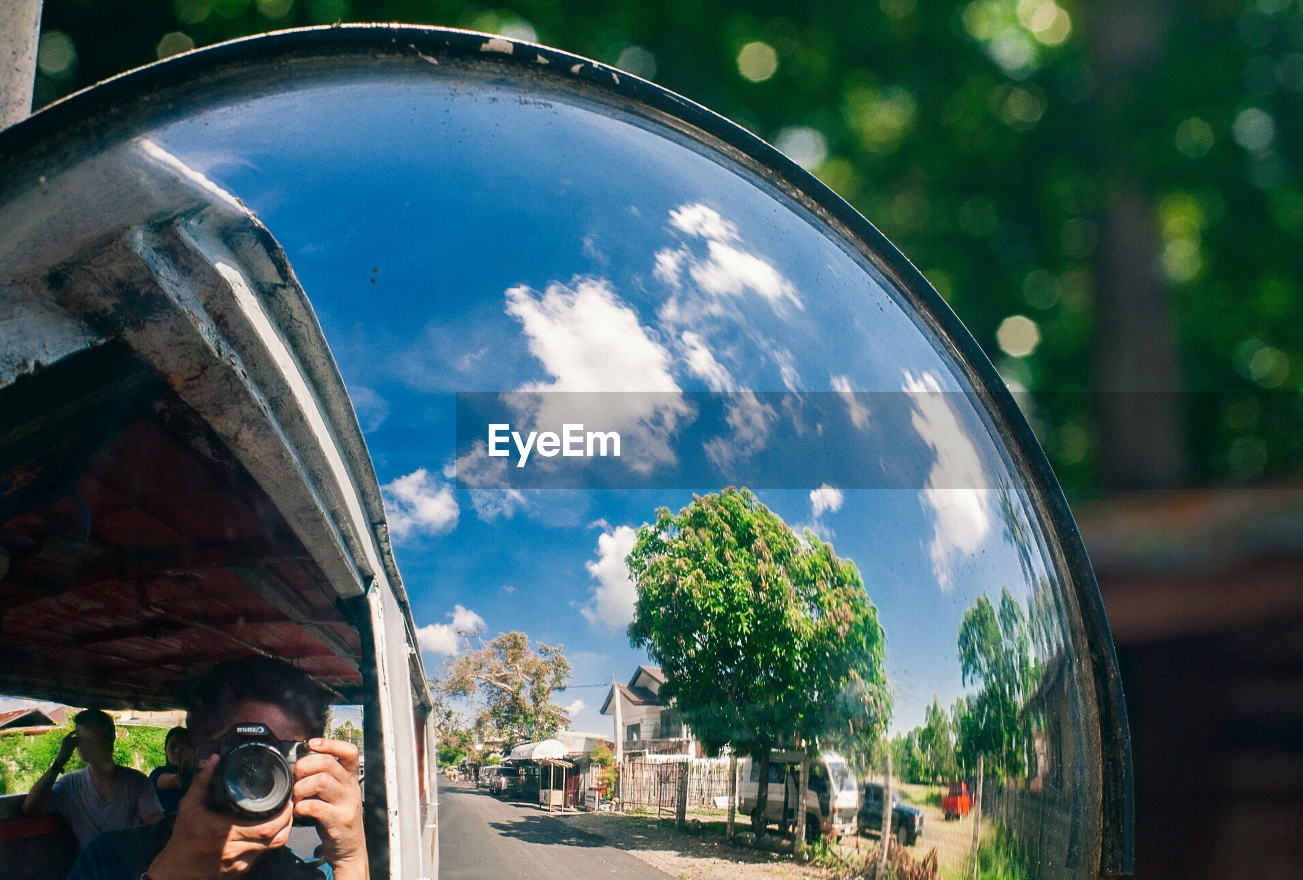 sky, car, land vehicle, transportation, cloud - sky, mode of transport, tree, reflection, cloud, fish-eye lens, street, built structure, glass - material, building exterior, architecture, transparent, day, blue