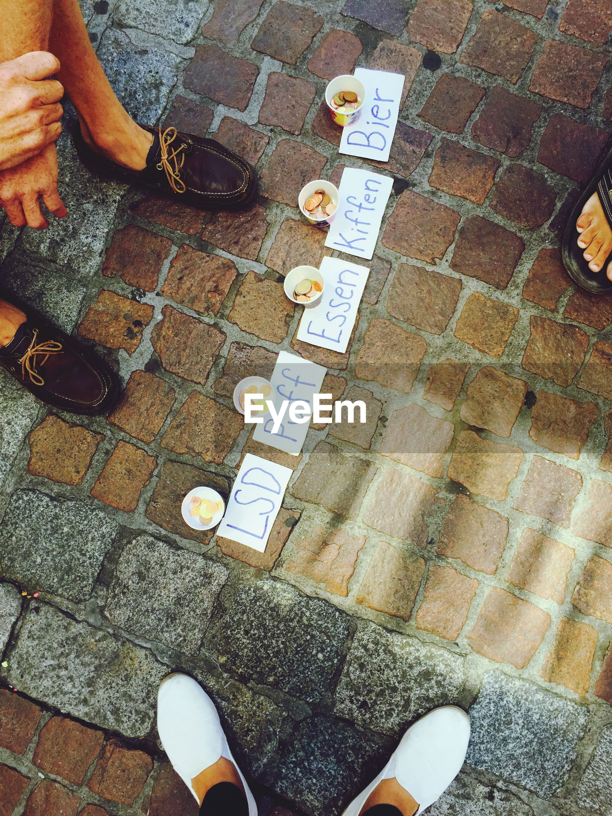 Cropped image of friends standing by candies on sidewalk with text