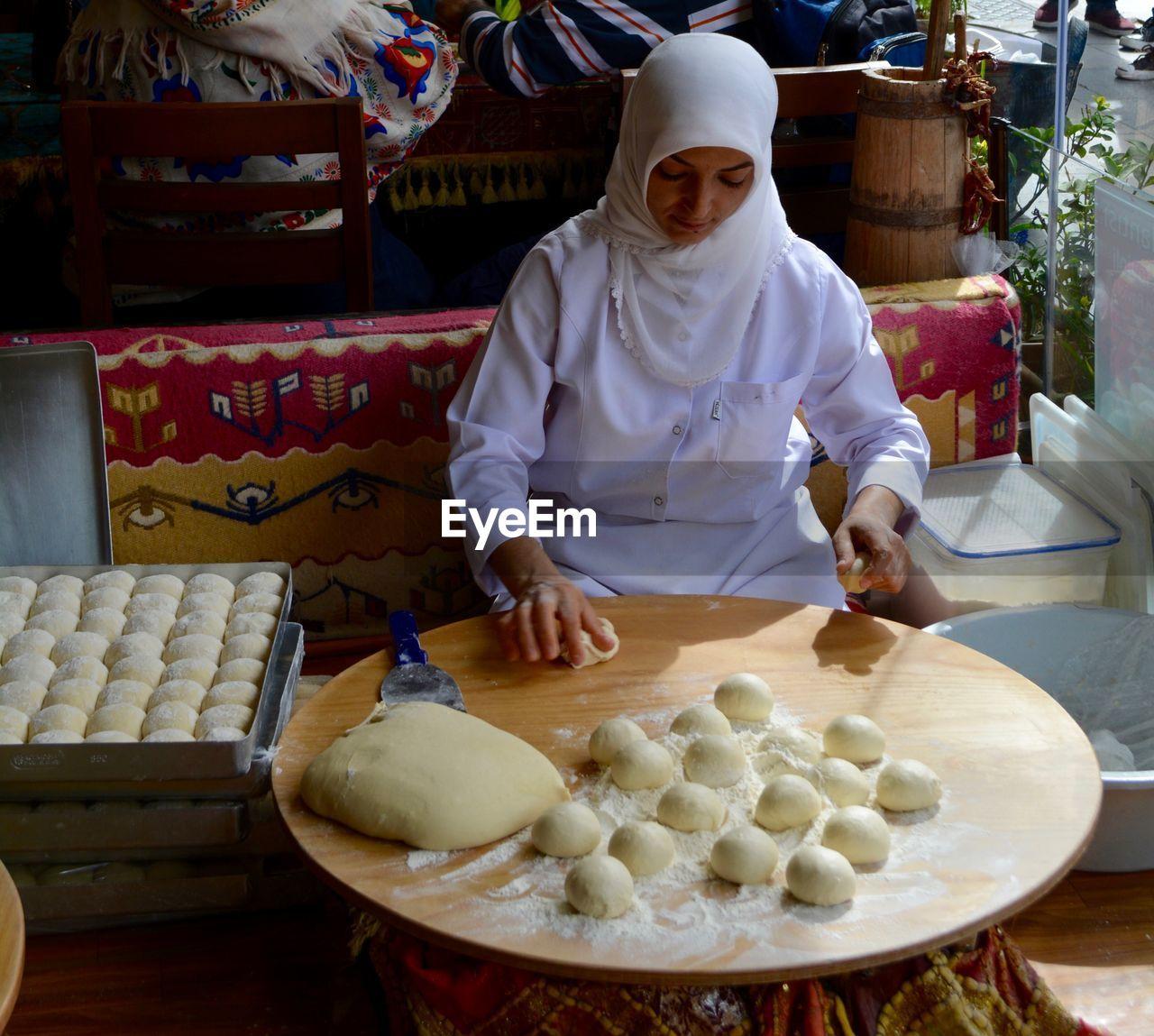 Woman Wearing Hijab Preparing Food In Bakery