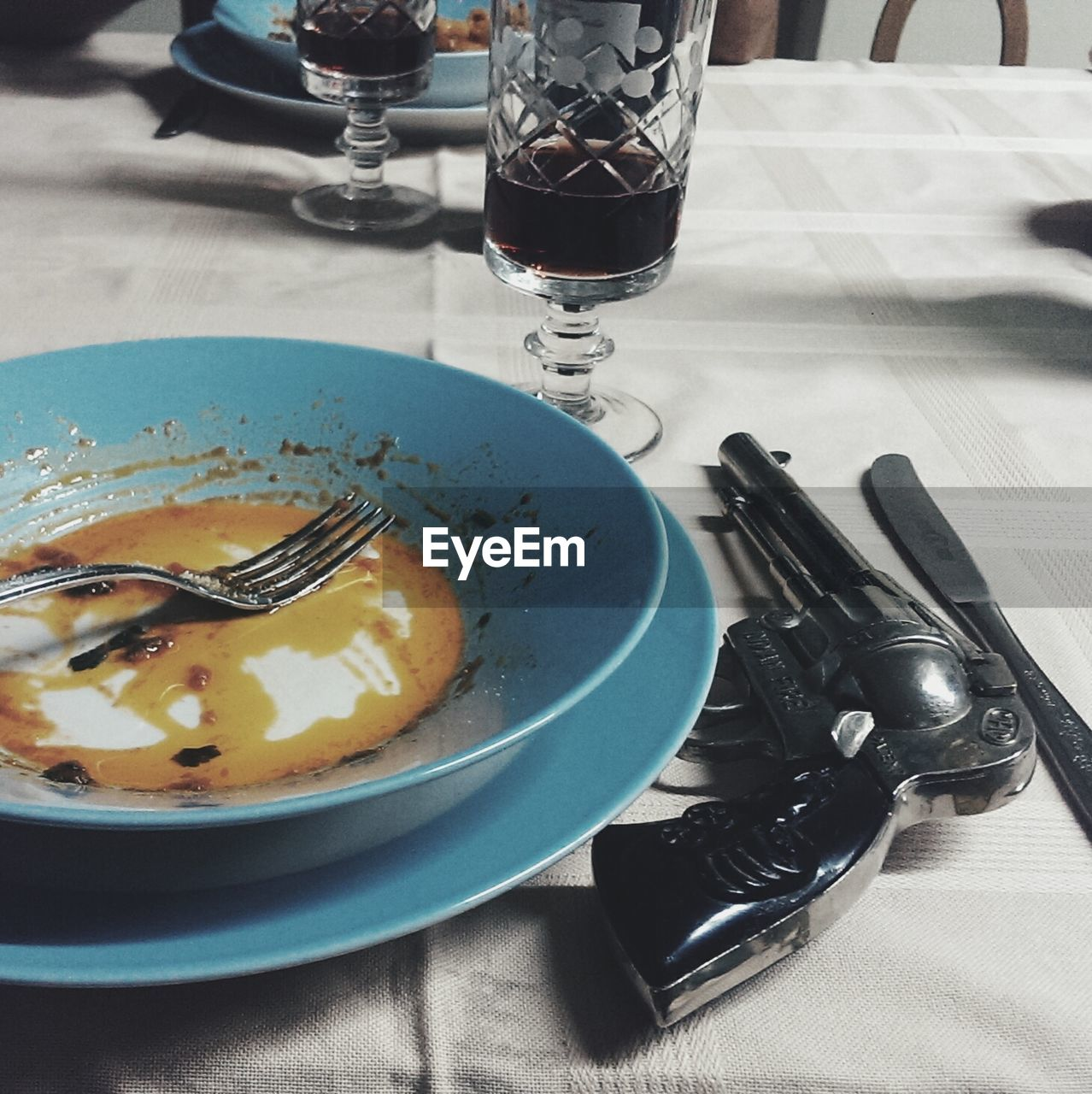 Gun By Leftovers In Bowl On Table