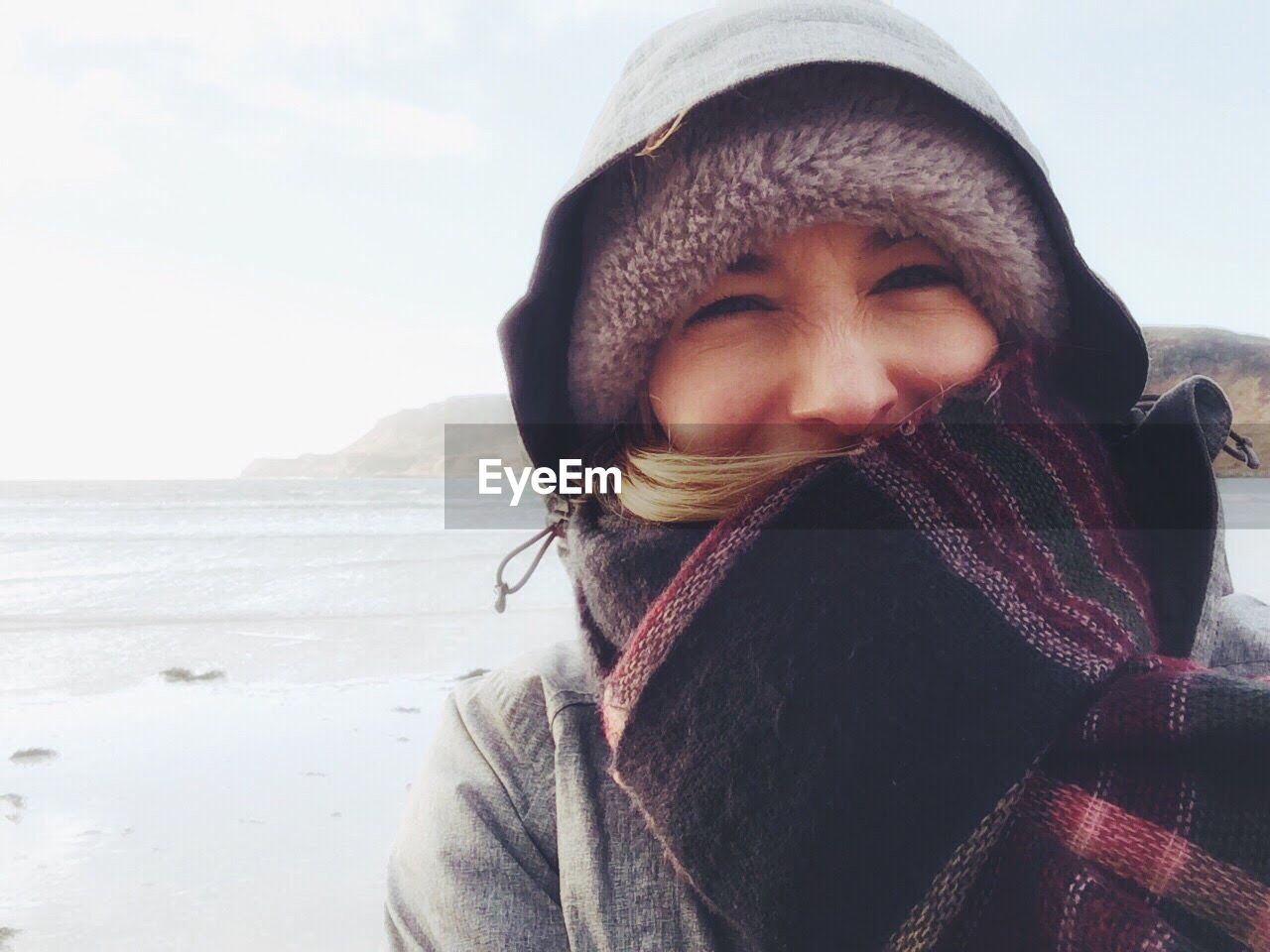 Portrait Of Young Woman In Warm Clothing Against Sea