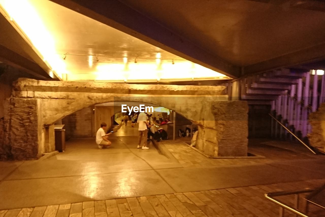 group of people, indoors, architecture, built structure, subway, illuminated, transportation, real people, women, public transportation, subway station, men, walking, ceiling, lifestyles, people, adult, flooring, travel, mode of transportation, architectural column, underground walkway
