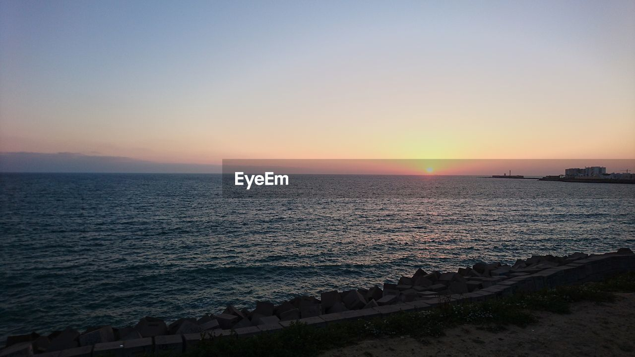 sunset, sea, beauty in nature, water, scenics, nature, tranquil scene, tranquility, sun, beach, idyllic, no people, clear sky, outdoors, horizon over water, sunlight, sky, wave, day