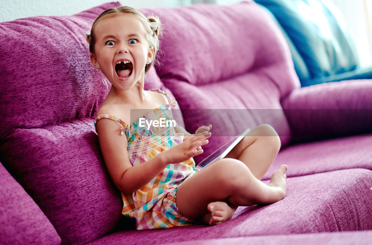Portrait of cute girl using digital tablet sitting on pink sofa with mouth open at home