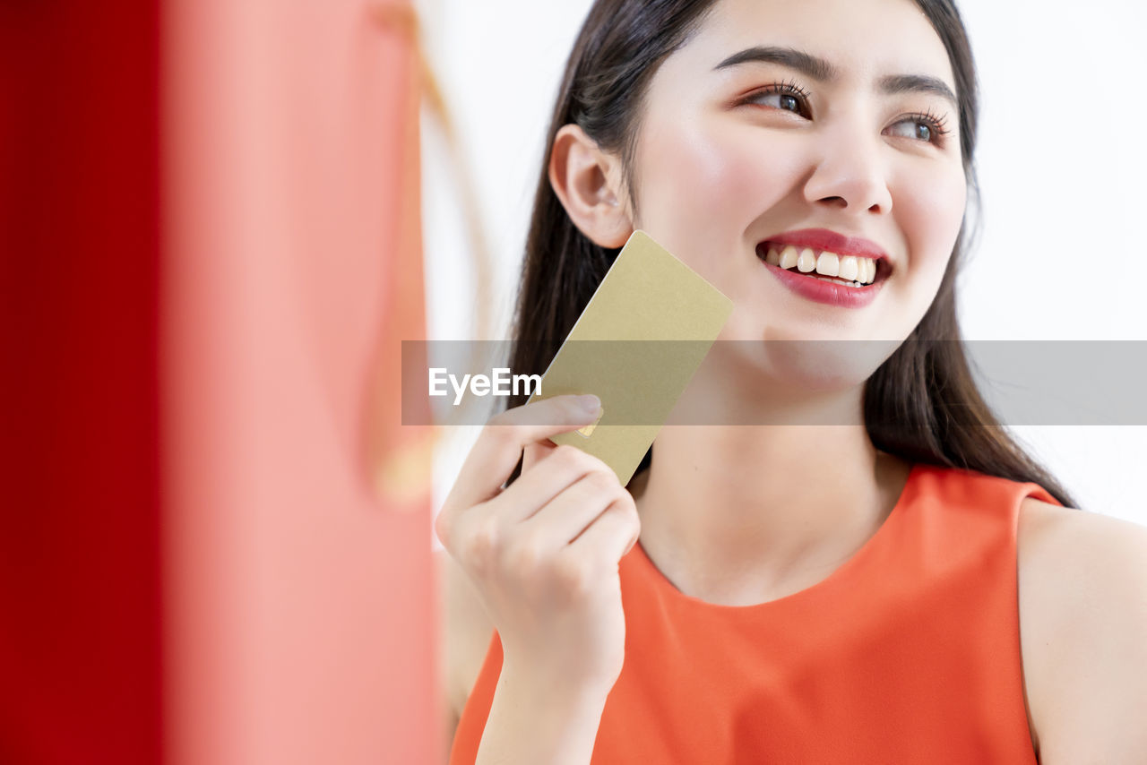 Smiling woman holding credit card and looking away