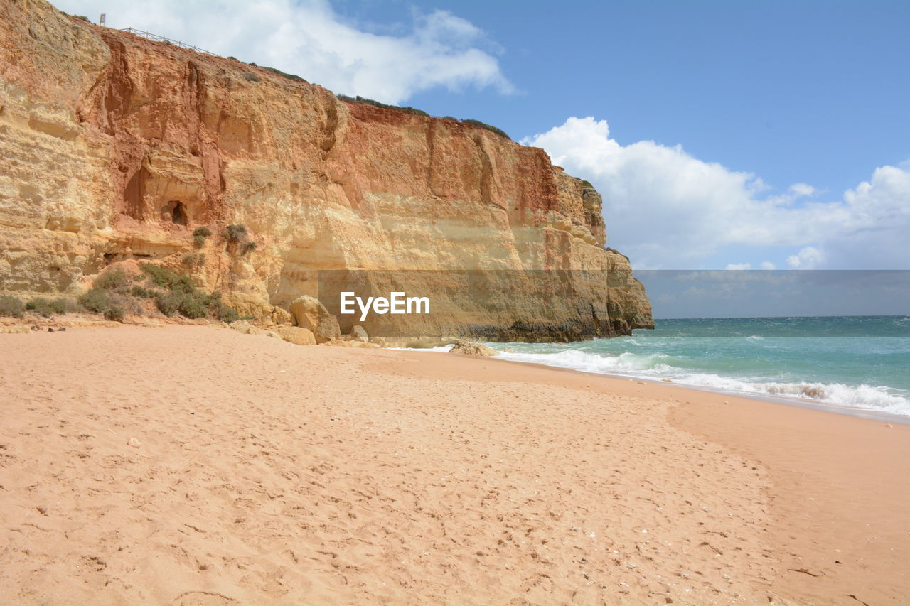 land, beach, sea, sky, water, sand, beauty in nature, scenics - nature, tranquility, cloud - sky, nature, rock, rock formation, tranquil scene, horizon, rock - object, horizon over water, day, solid, no people, outdoors