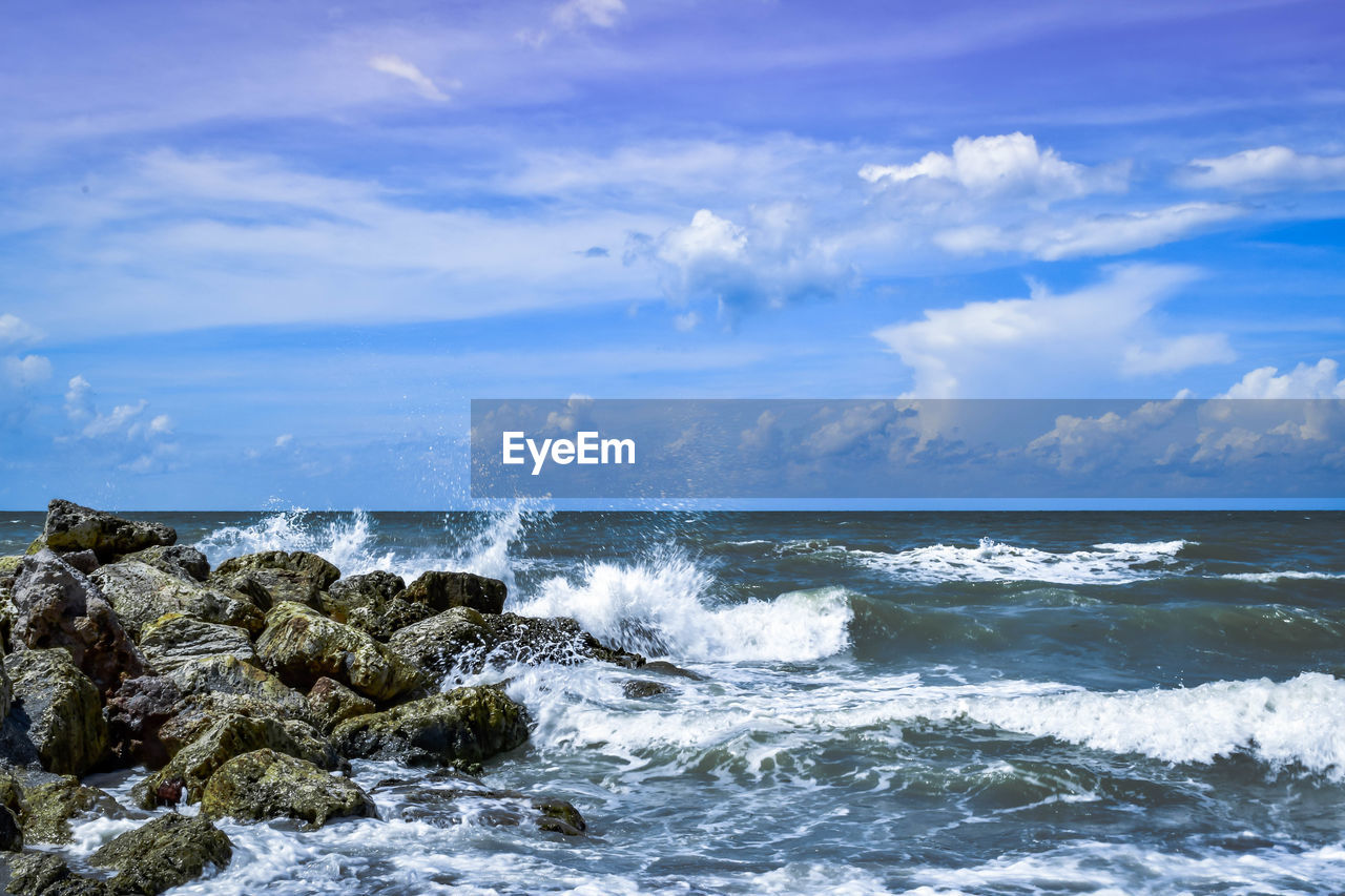 Waves splashing on rock shore against sky