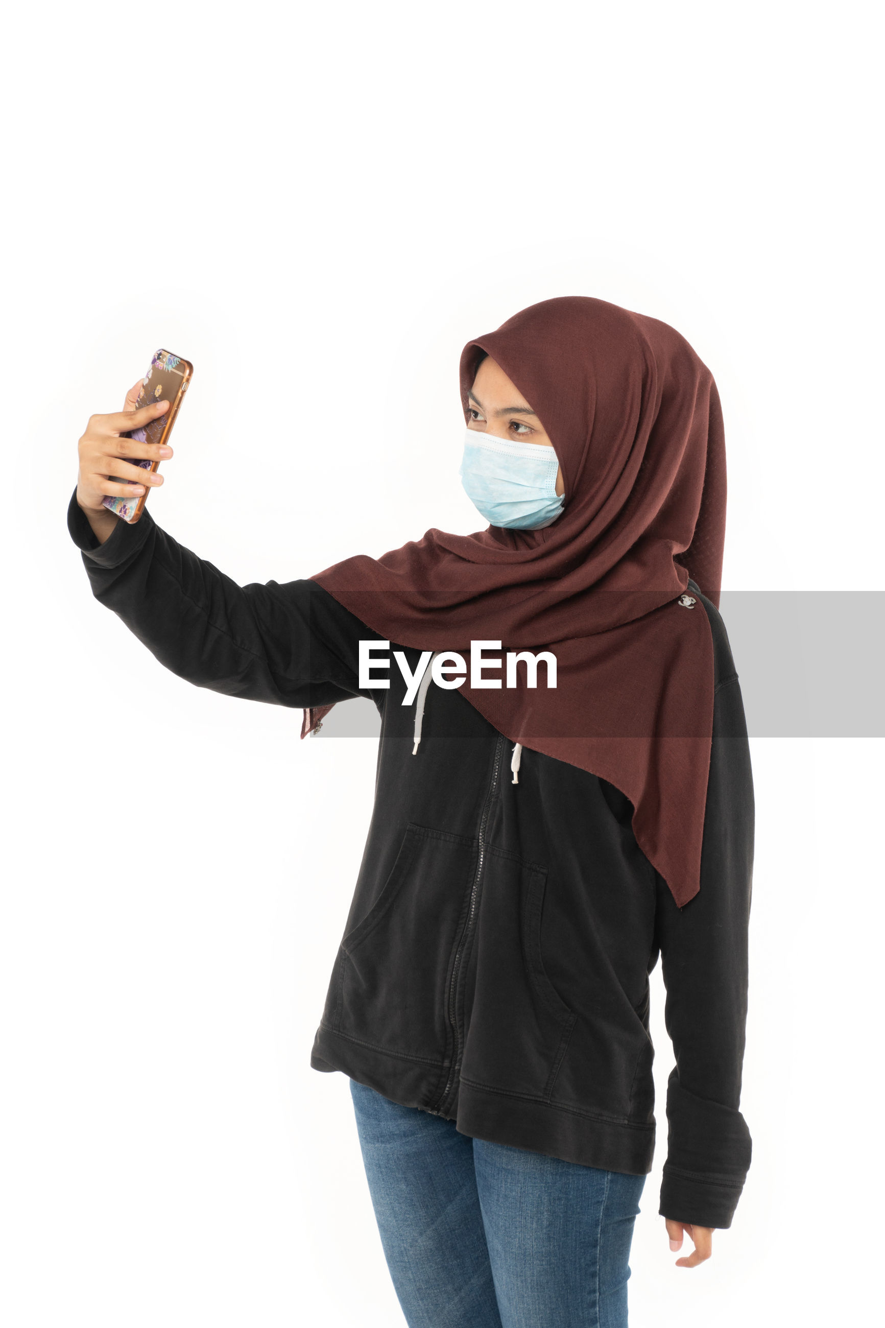 Woman in hijab wearing pollution mask while taking selfie against white background