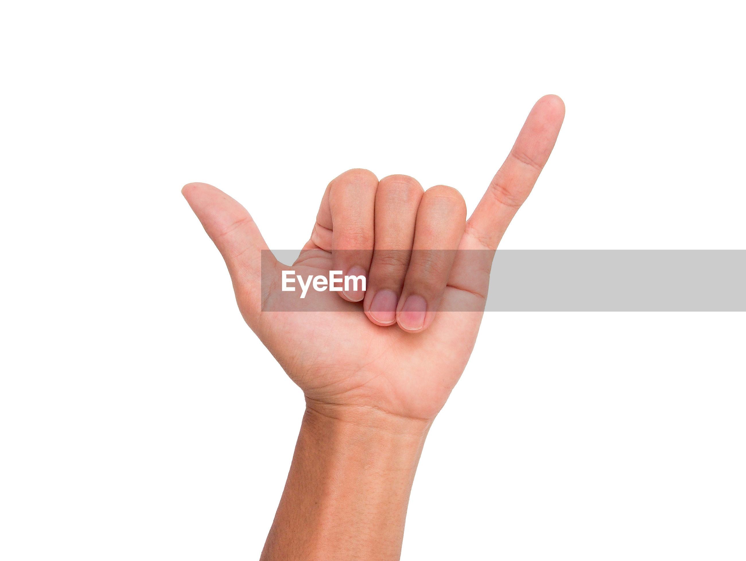 Cropped image of person showing shaka sign against white background