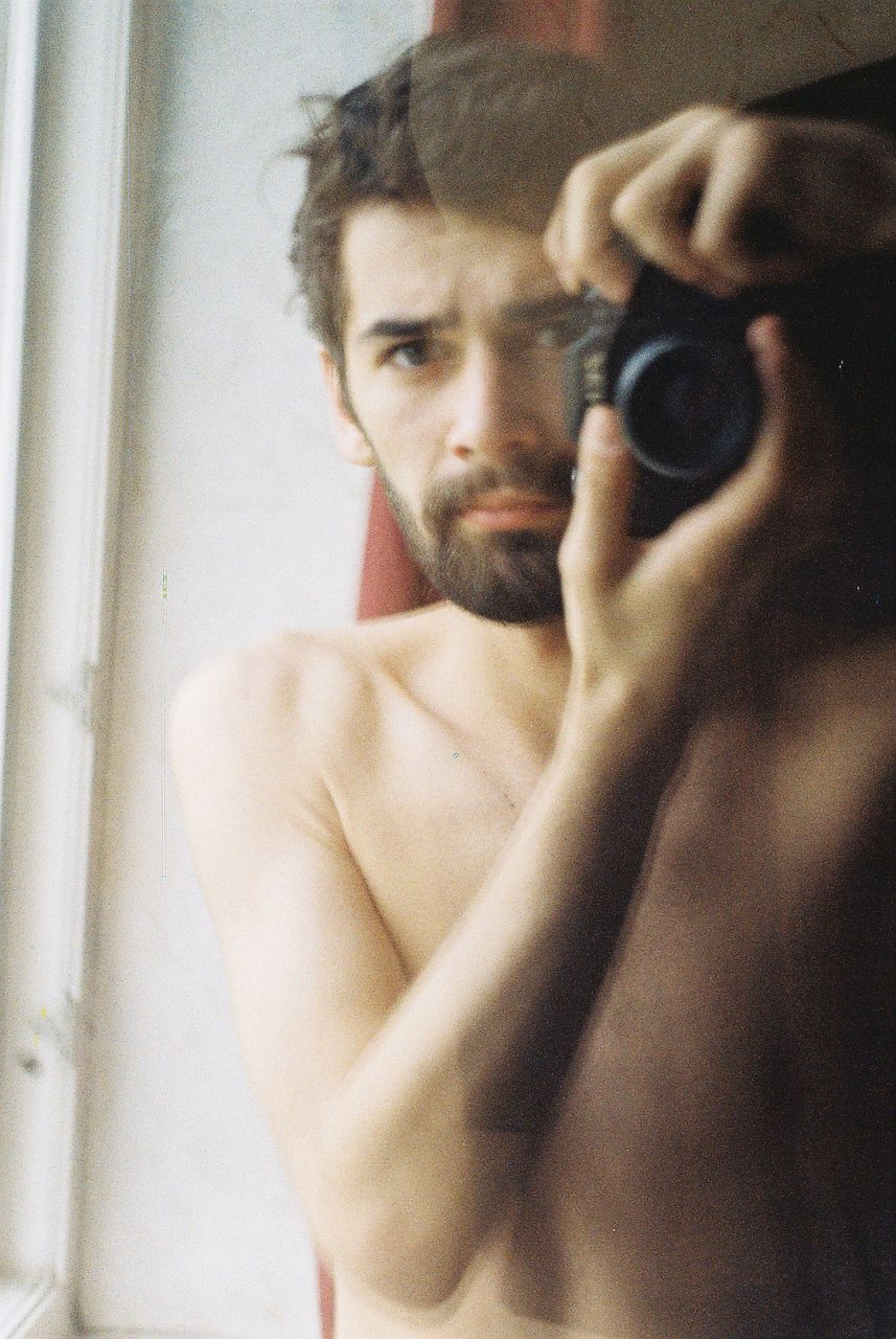 Reflection of shirtless young man photographing on mirror