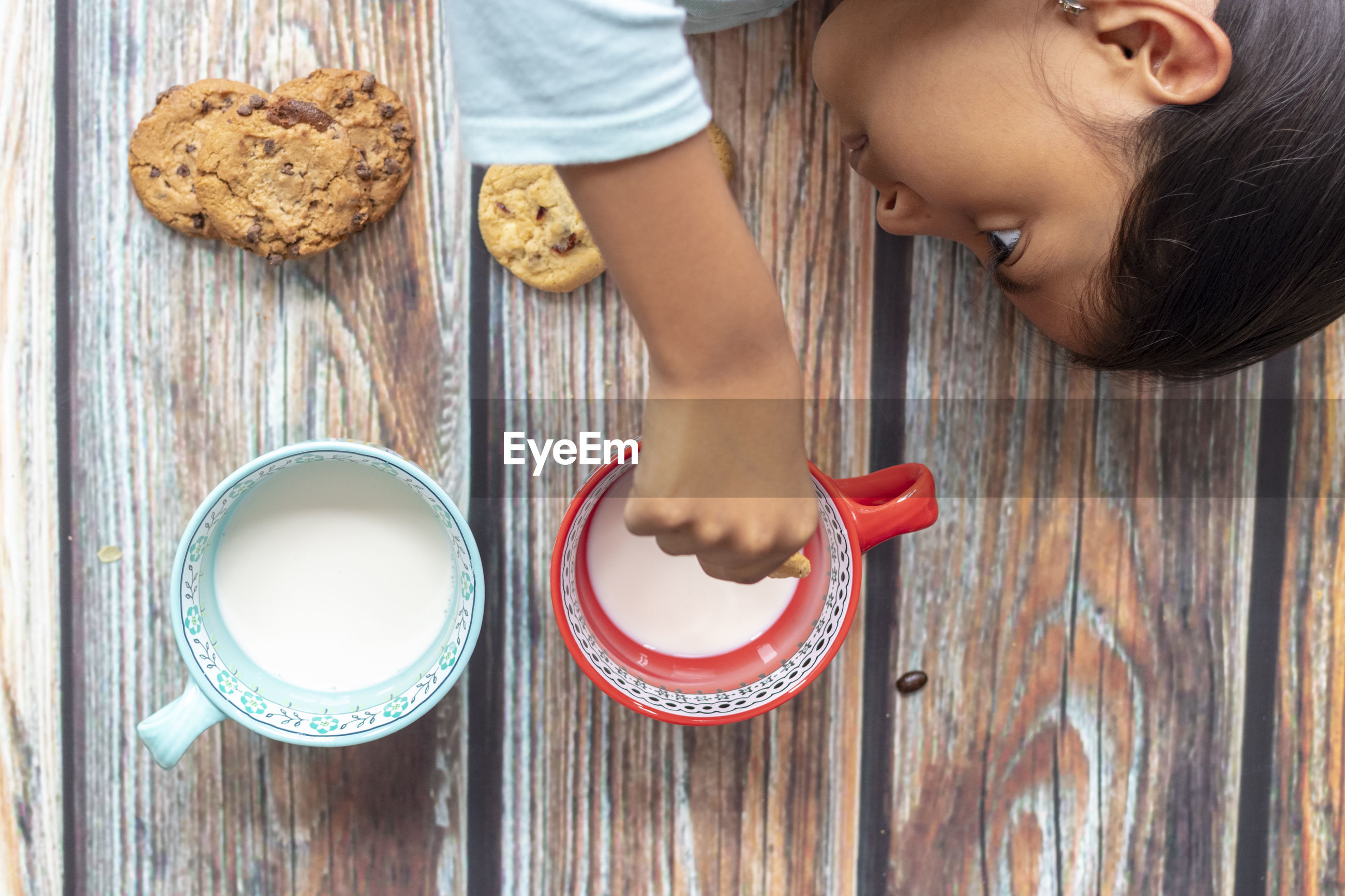 High angle view of girl holding cookies on wooden table