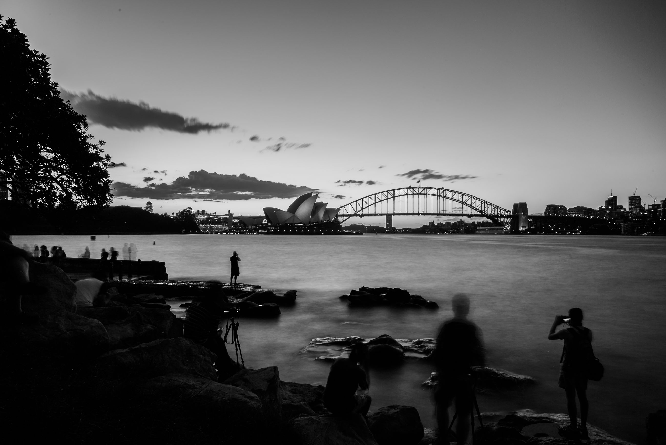 Sydney opera house by bridge in front of river against sky at dusk