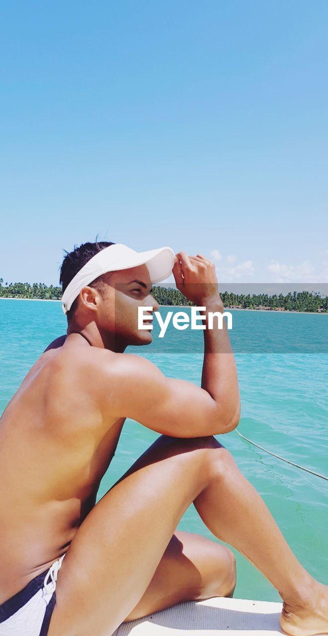 Shirtless man sitting at beach against blue sky