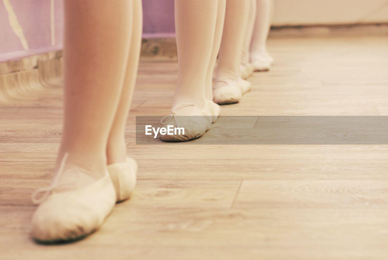 Low Section Of Ballet Dancer Standing On Hardwood Floor