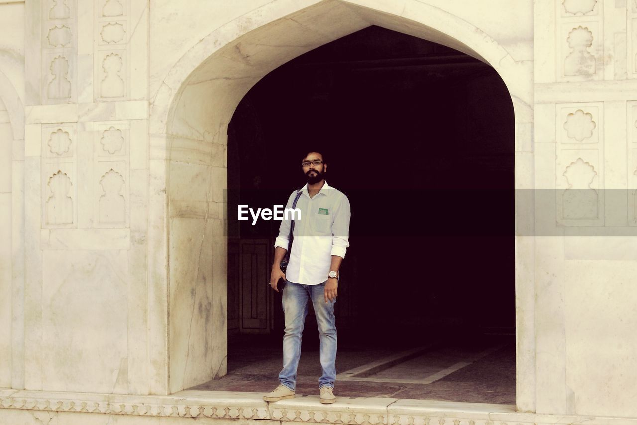 arch, architecture, one person, full length, real people, casual clothing, front view, standing, looking at camera, portrait, built structure, doorway, day, architectural column, lifestyles, building exterior, indoors, one man only, young adult, adult, adults only, people