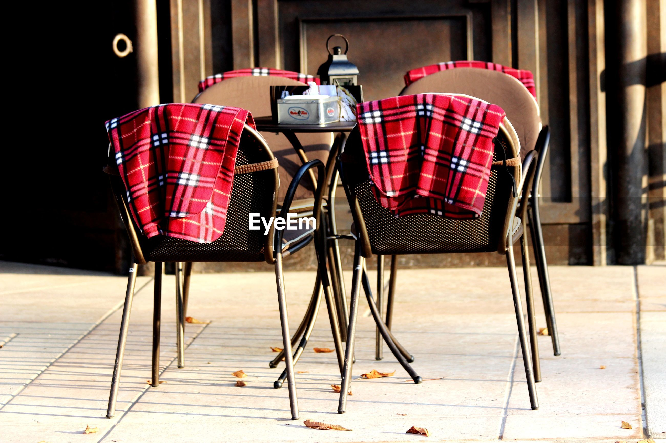 EMPTY CHAIRS AND TABLE IN CAFE AGAINST BUILDING