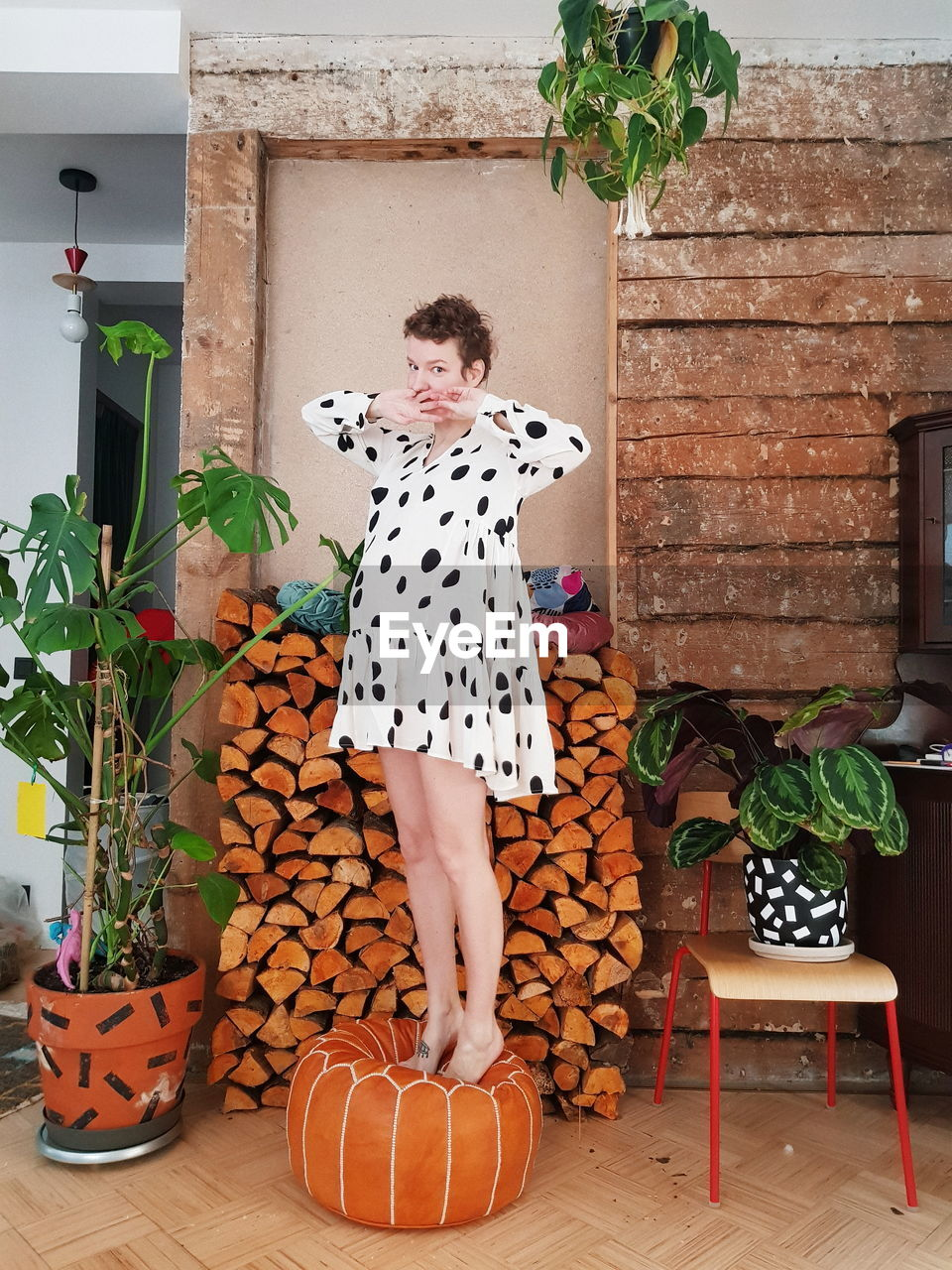 MIDSECTION OF WOMAN STANDING BY POTTED PLANTS