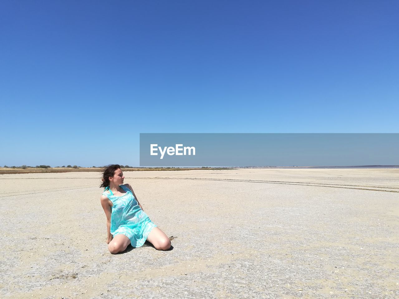 Mature Woman Looking Away While Sitting On Sand Dune Against Clear Sky During Sunny Day