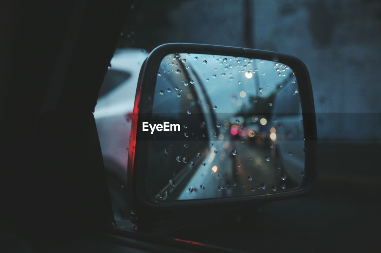 Reflection Of Cars On Wet Side-View Mirror