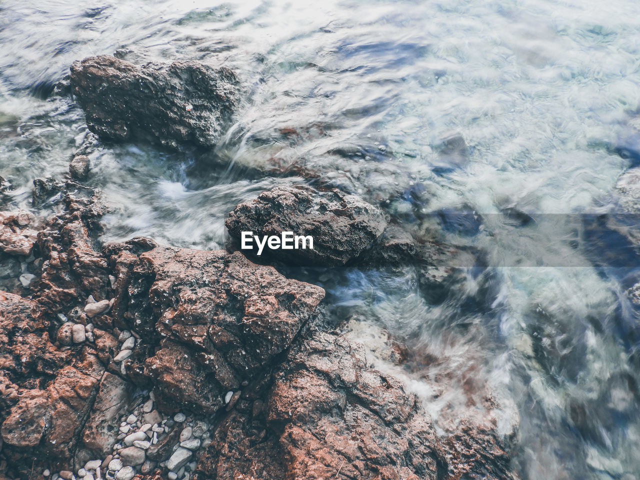 High angle view of sea water flowing on rocks