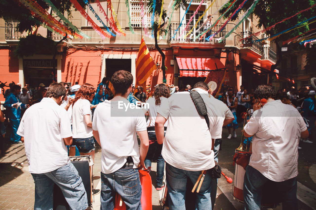 Rear view of men performing at festa major de gracia in city