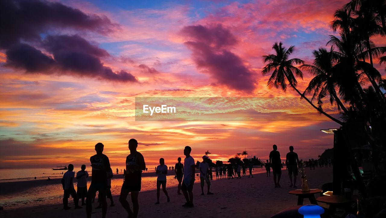 sunset, beach, sea, sky, cloud - sky, nature, silhouette, horizon over water, orange color, scenics, beauty in nature, water, sand, large group of people, vacations, palm tree, outdoors, tranquil scene, men, leisure activity, tranquility, real people, tree, beach volleyball, people