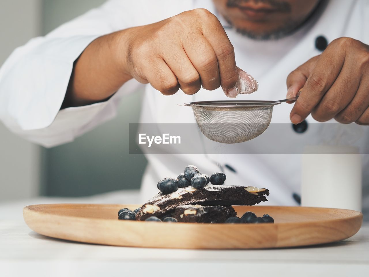 Midsection of chef garnishing dessert