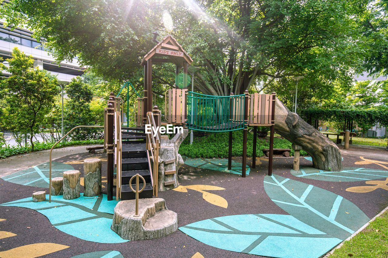 tree, plant, sunlight, nature, day, architecture, playground, park, no people, swimming pool, built structure, pool, outdoors, park - man made space, absence, front or back yard, wood - material, green color, grass, outdoor play equipment