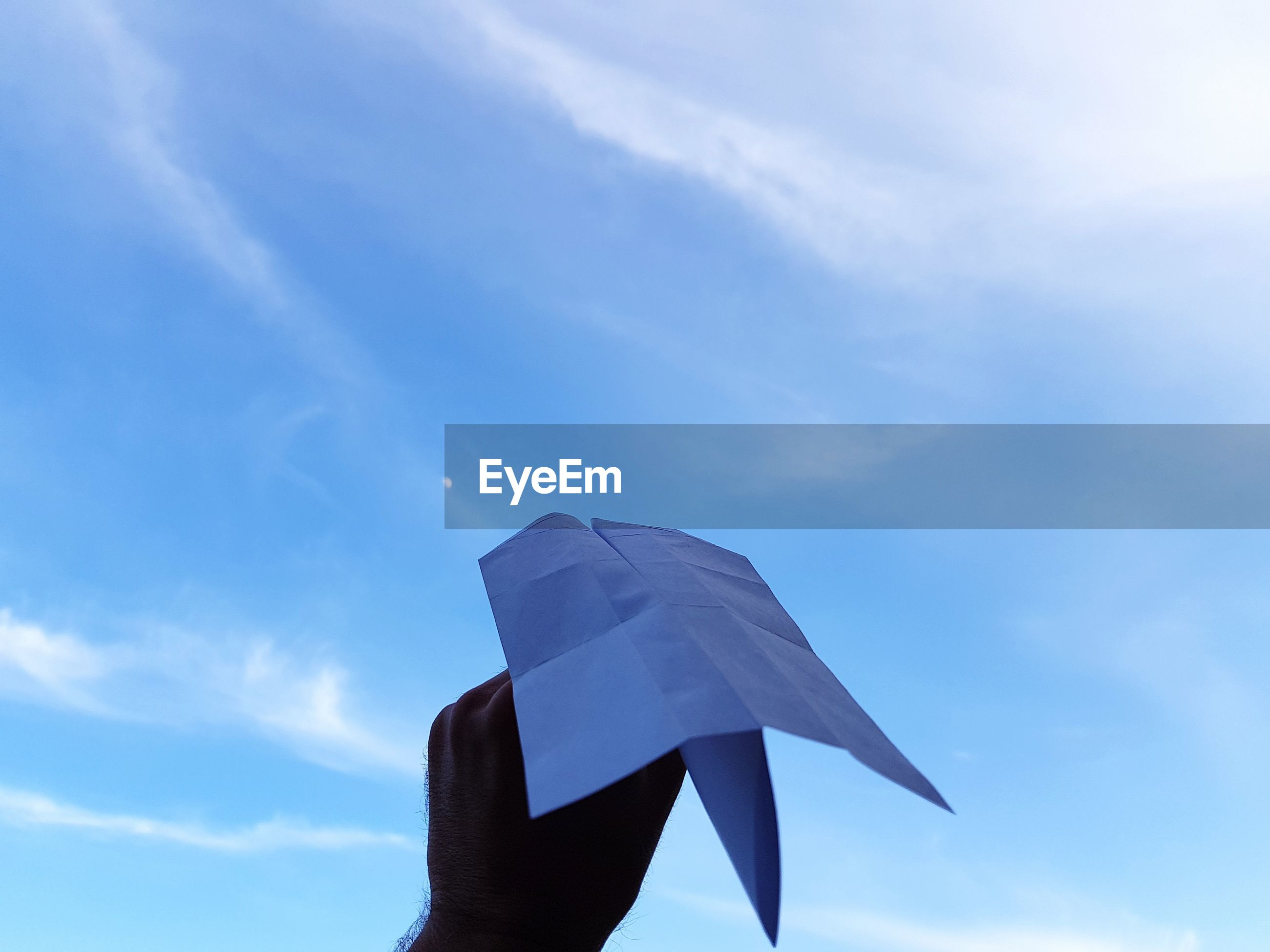 Low angle view of hand holding paper airplane against sky