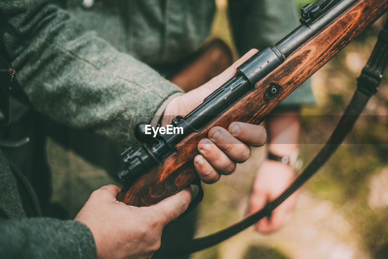 human hand, holding, gun, hand, weapon, real people, focus on foreground, close-up, one person, aiming, human body part, men, day, rifle, sport, protection, accuracy, safety, outdoors