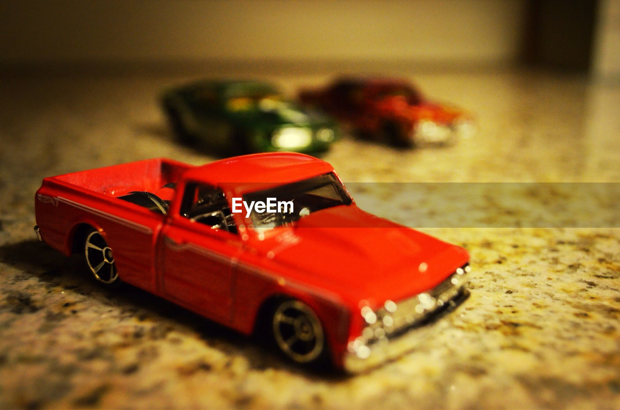 red, selective focus, focus on foreground, toy, close-up, still life, transportation, single object, land vehicle, surface level, mode of transport, day, no people, sunlight, outdoors, sand, abandoned, childhood, car, street