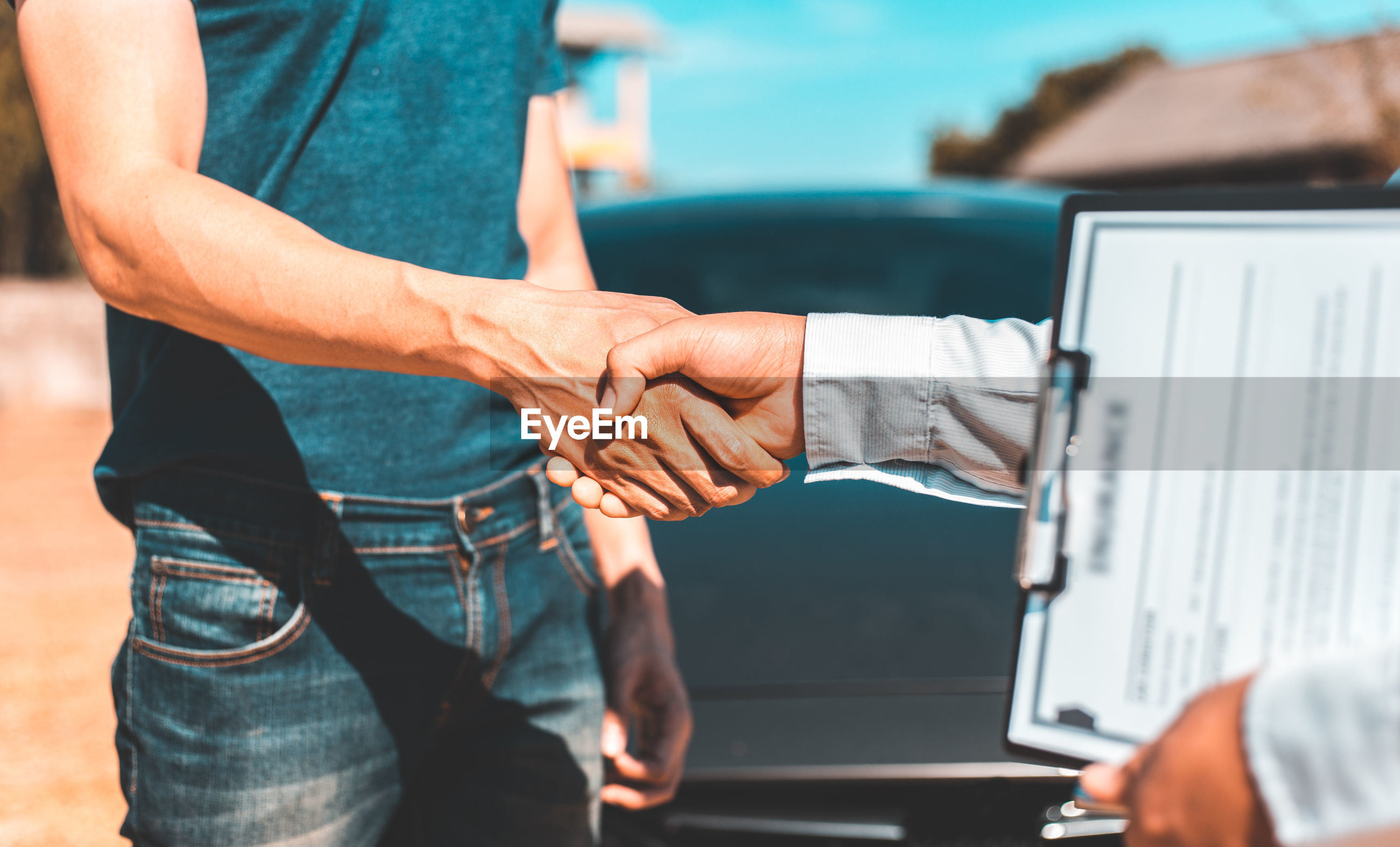Midsection of man and agent shaking hands while standing by cars