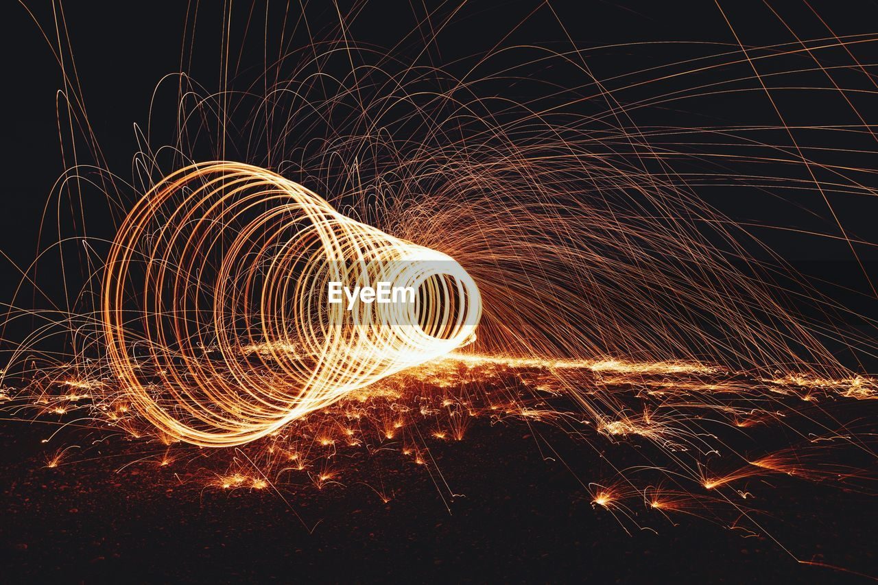 night, long exposure, wire wool, motion, illuminated, spinning, blurred motion, glowing, pattern, light painting, sparks, shape, orange color, circle, light trail, creativity, speed, geometric shape, nature, spiral, no people, abstract, outdoors, light