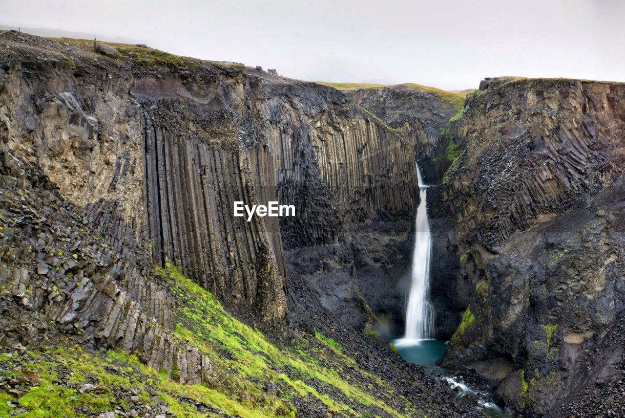 waterfall, rock - object, nature, scenics, mountain, no people, water, outdoors, river, motion, tranquil scene, beauty in nature, cliff, day, power in nature, landscape, sky
