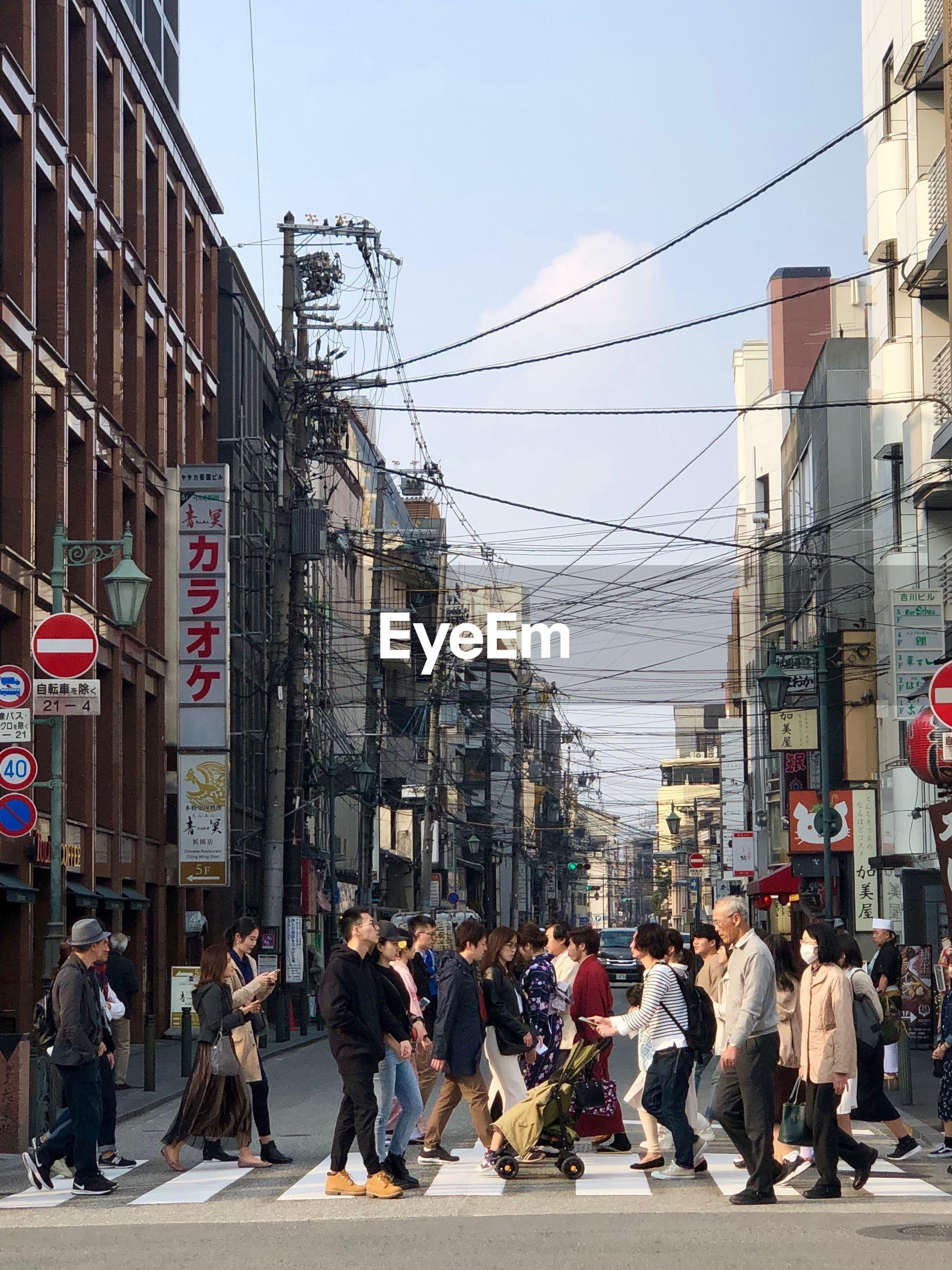 GROUP OF PEOPLE WALKING ON STREET AGAINST BUILDINGS