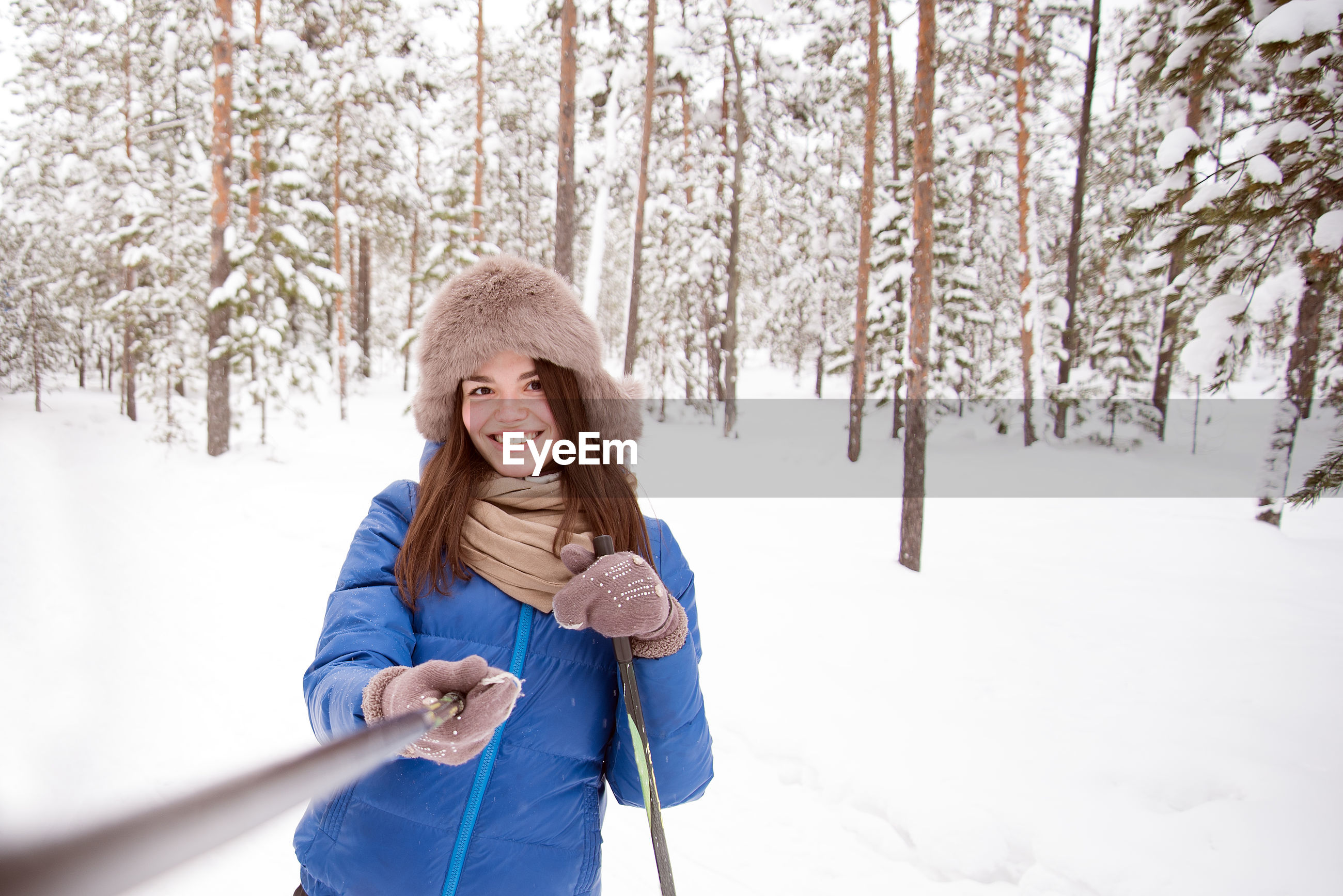 Portrait of smiling woman standing on snow covered land