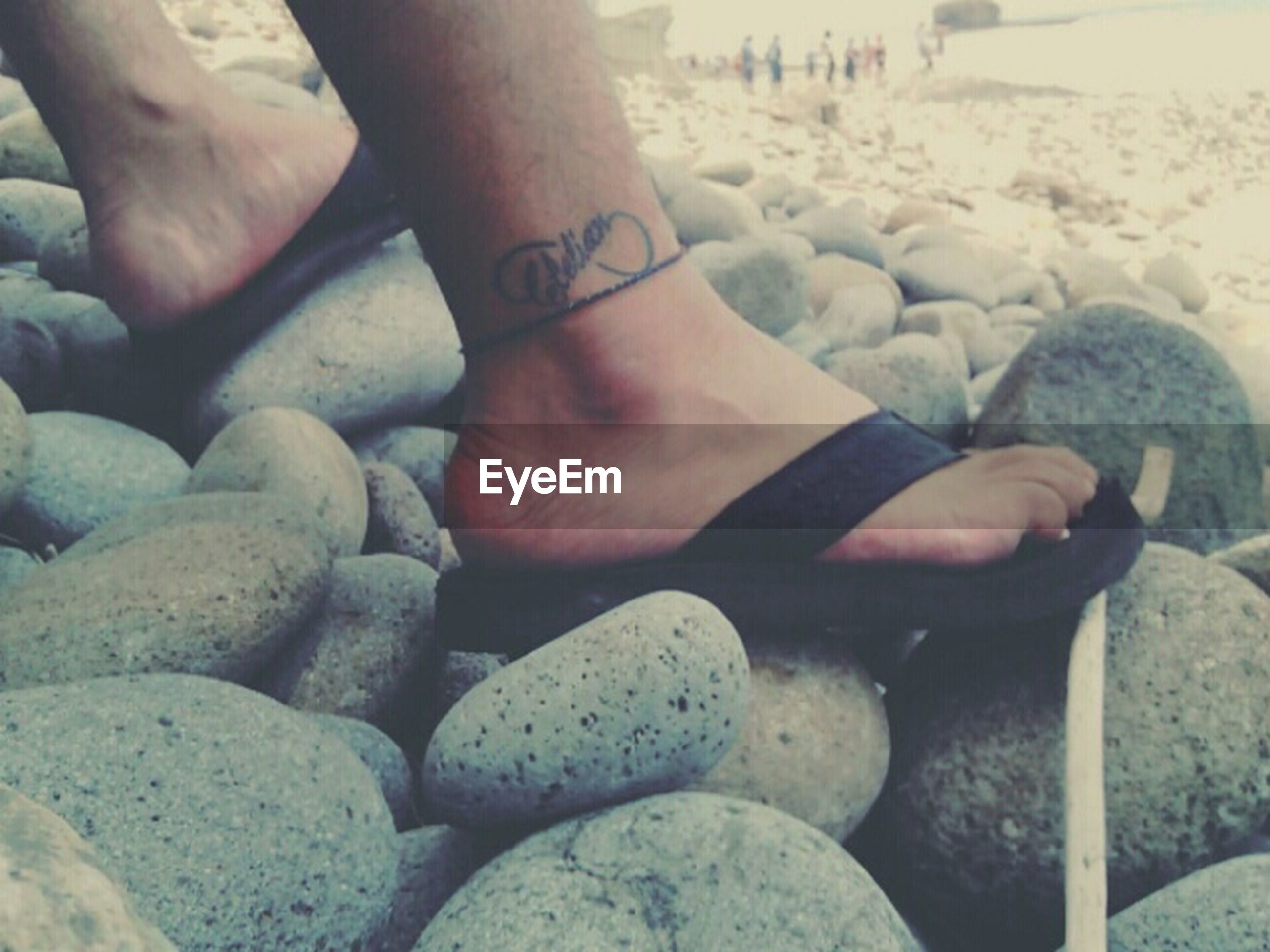 beach, low section, sand, lifestyles, person, shore, leisure activity, barefoot, pebble, stone - object, water, sea, rock - object, human foot, vacations, standing