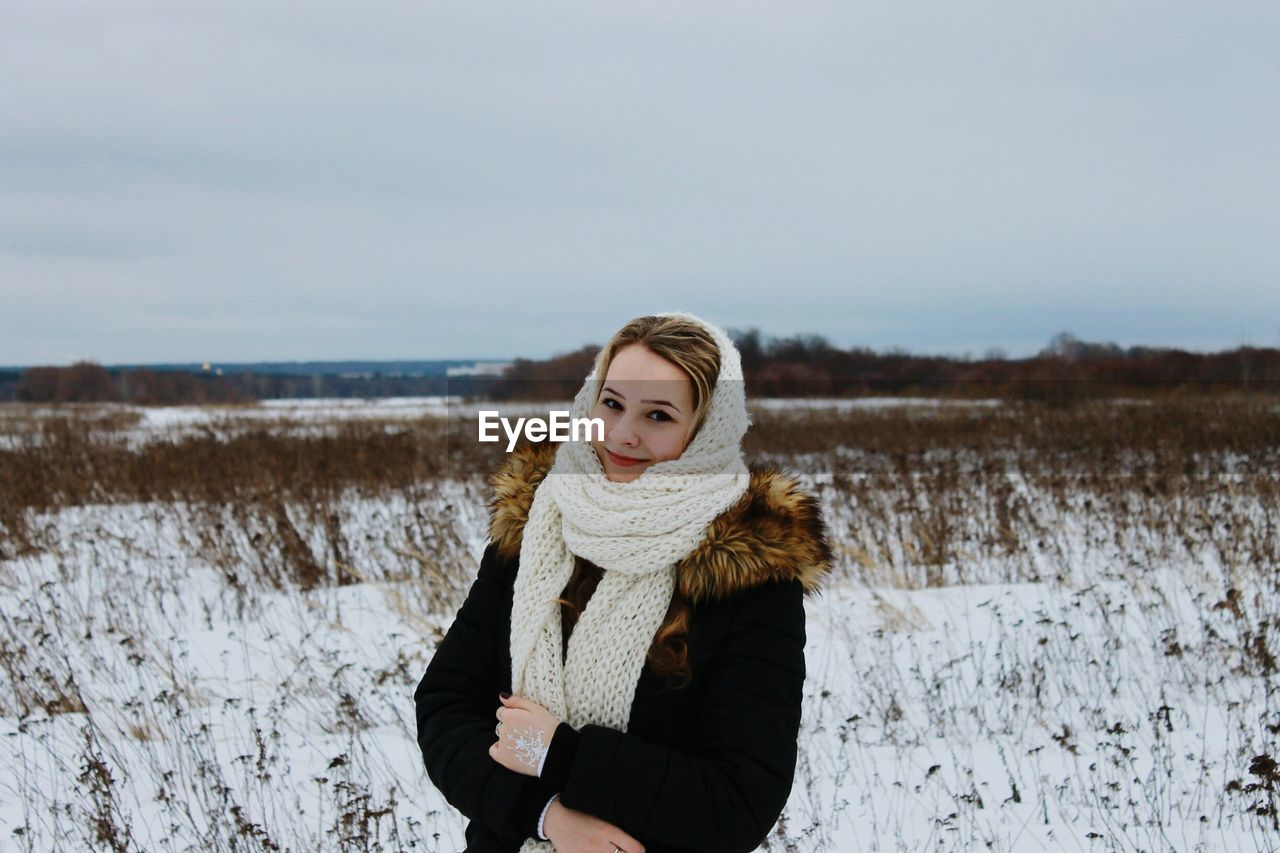 Portrait Of Woman Standing On Snow Covered Field