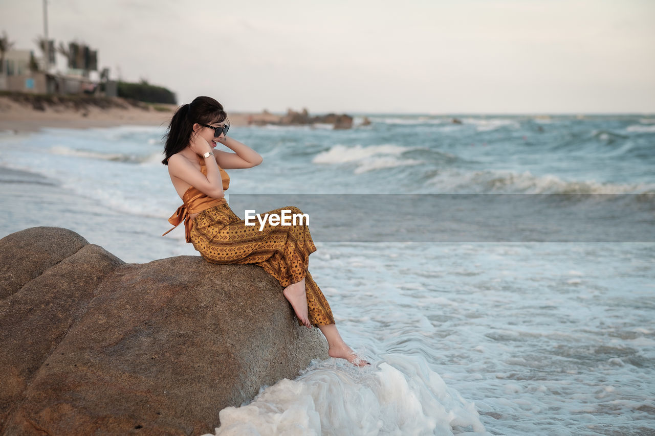 Woman sitting on rock at beach against sky